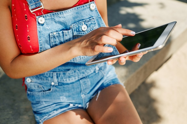 Jonge blonde vrouw zittend in het park en met behulp van tablet