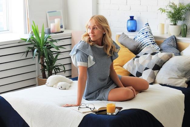 Jonge blonde vrouw zittend op bed met een laptop en een glas sap, freelancer thuis.