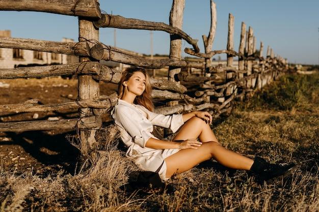 Jonge blonde vrouw zittend op de grond, naast een houten hek op een boerderij
