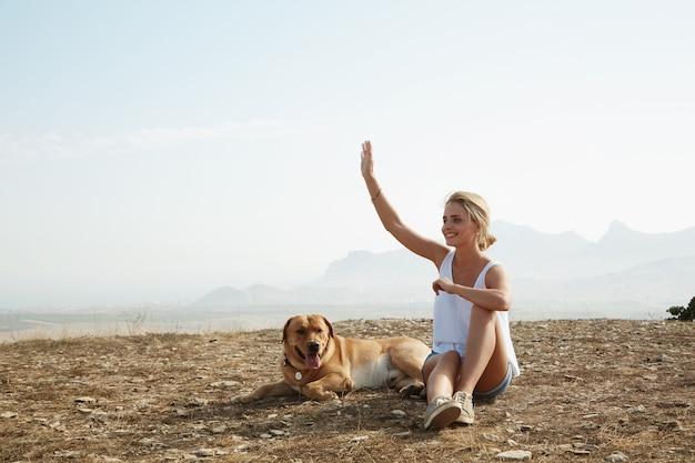 Jonge blonde vrouw zittend op de top van de heuvel
