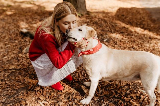 Jonge blonde vrouw zoenen teder schattige hond. mooi meisje met haar huisdierenzitting tussen gevallen bladeren.