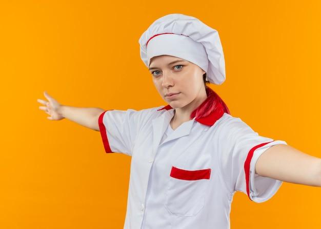 Jonge blonde vrouwelijke chef-kok in chef-kok uniforme stands met open armen geïsoleerd op oranje muur