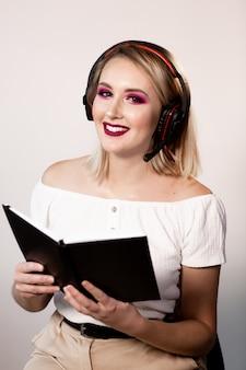 Jonge blonde vrouwelijke exploitant in hoofdtelefoons met notitieboekje op lichte achtergrond. bespotten