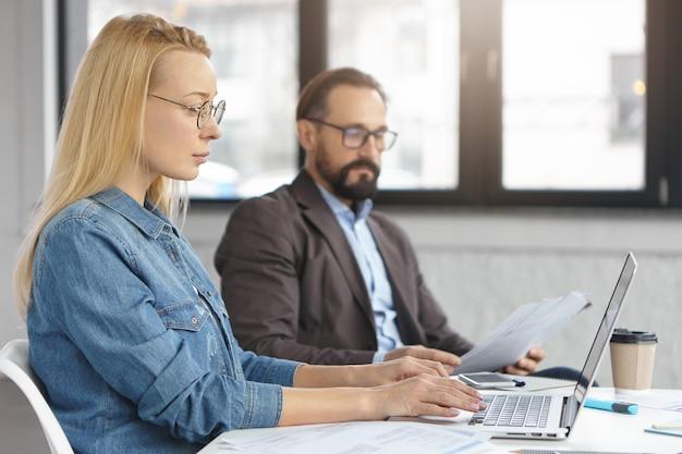 Jonge blonde vrouwelijke it-ontwikkelaar test nieuwe softwaretoepassing op laptopcomputer