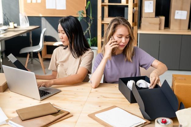 Jonge blonde vrouwelijke manager van online winkelkantoor die met klanten op mobiele telefoon praat en koptelefoons in een zwarte doos zet op de werkplek