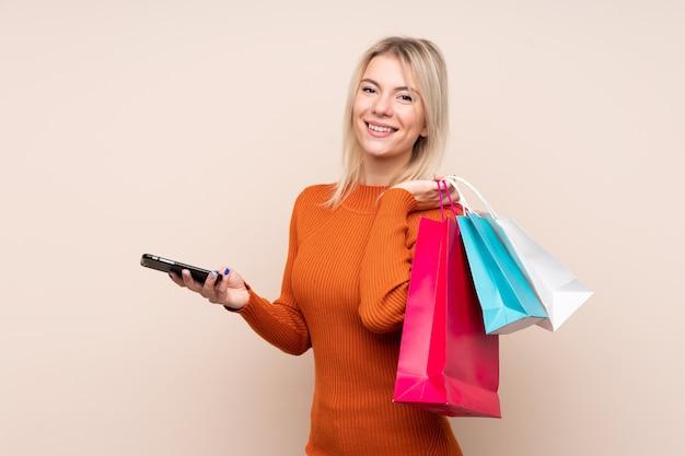 Jonge blonde vrouwenholding het winkelen zakken en het schrijven van een bericht met haar celtelefoon aan een vriend