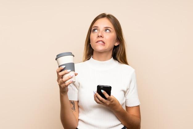 Jonge blonde vrouwenholding koffie om weg te halen en mobiel terwijl het denken van iets