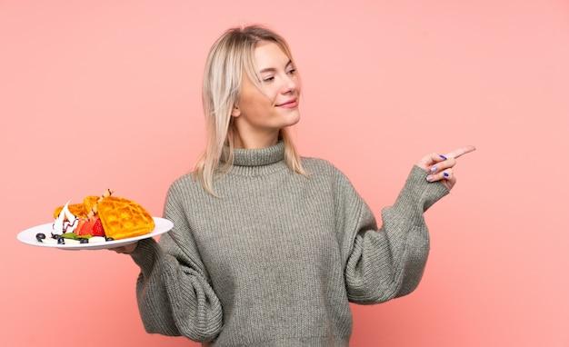 Jonge blonde vrouwenholdingswafels over geïsoleerde roze muur die aan de kant richten om een product te presenteren