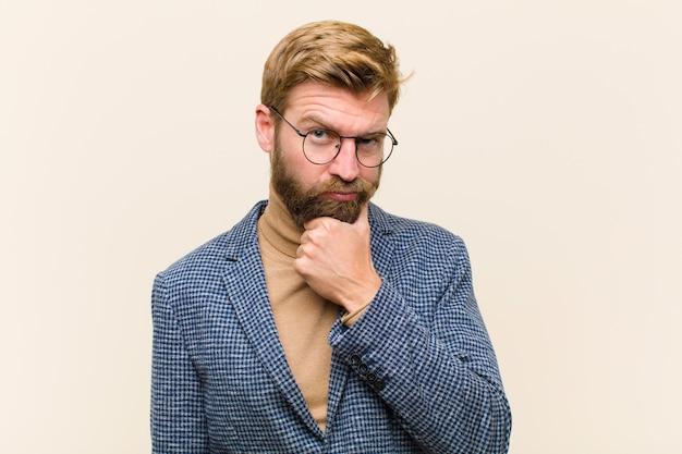 Jonge blonde zakenman die ernstig, verward, onzeker en nadenkend kijkt, twijfelend onder optionschoices