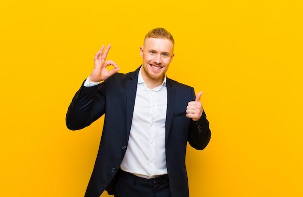 Jonge blonde zakenman die gelukkig, verbaasd, tevreden en verrast, ok tonen en duimen op gebaren, het glimlachen voelen