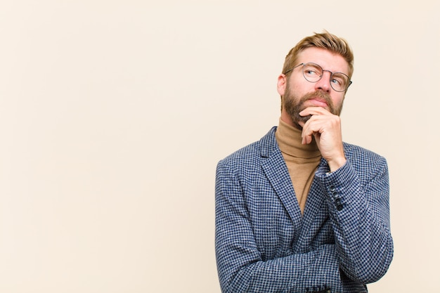 Jonge blonde zakenman die nadenkend voelen, ideeën benieuwd zijn of verbeelden, dagdromen en omhoog kijken om ruimte te kopiëren