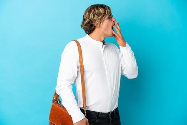 Jonge blonde zakenman die op blauwe muur wordt geïsoleerd die en wijd open mond behandelt met hand