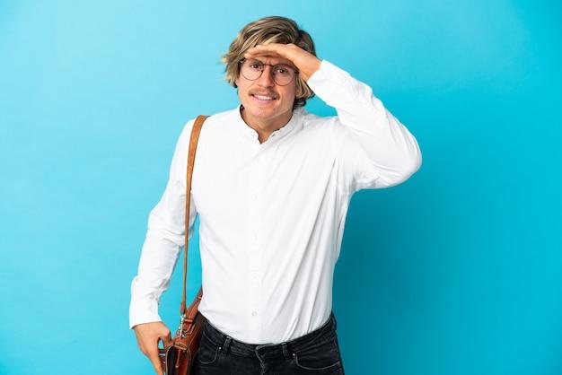 Jonge blonde zakenman die op blauwe muur wordt geïsoleerd die ver weg met hand kijkt om iets te kijken
