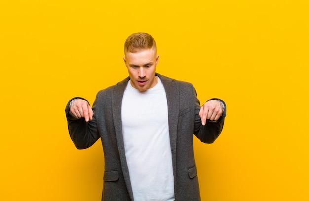 Jonge blonde zakenman gevoel geschokt, met open mond en verbaasd, naar beneden kijkend en wijzend in ongeloof en verbazing