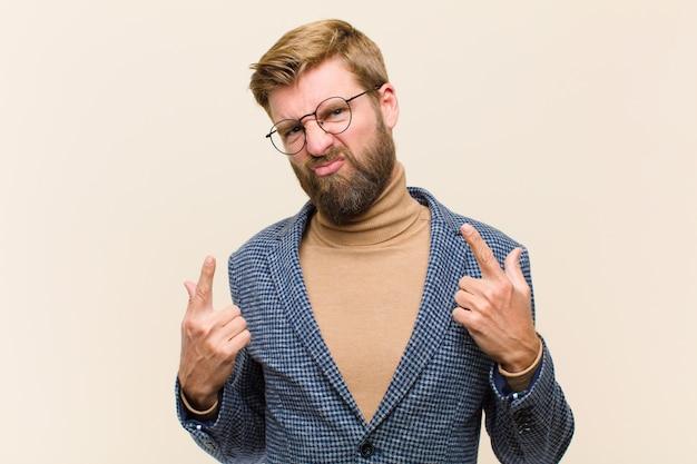 Jonge blonde zakenman met een slechte houding die trots en agressief kijkt, naar boven richt of leuk teken met handen maakt