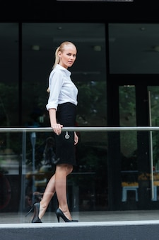 Jonge blonde zakenvrouw die op het glazen balkon staat en buiten naar de camera kijkt