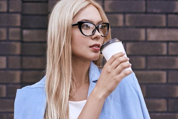 Jonge blonde zakenvrouw koffie drinken