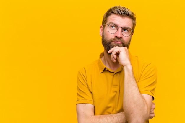 Jonge blondeman denken, twijfelachtig en verward voelen, met verschillende opties, zich afvragend welke beslissing te nemen tegen oranje muur