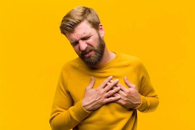 Jonge blondeman die droevig, gekwetst en diepbedroefd kijkt, beide handen dicht bij het hart houdt, huilend en depressieve oranje muur voelt