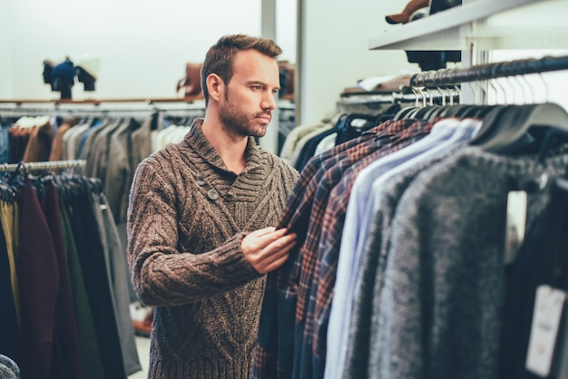 Jonge blondeman doen winkelen in een winkel