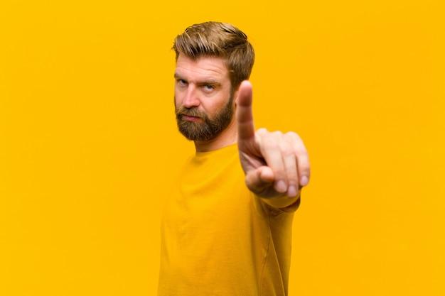 Jonge blondeman glimlachend trots en vol vertrouwen waardoor nummer één triomfantelijk poseert, voelend als een leider tegen oranje muur