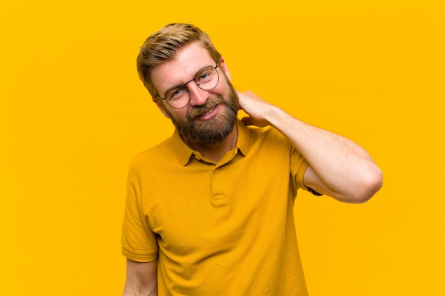 Jonge blondeman lachen vrolijk en vol vertrouwen met een ongedwongen, gelukkige, vriendelijke glimlach tegen oranje muur