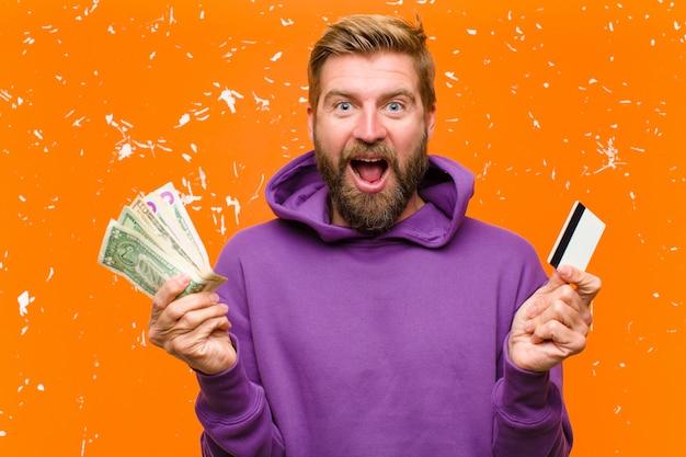 Jonge blondeman met een creditcard die een paarse hoodie draagt tegen beschadigde oranje muur