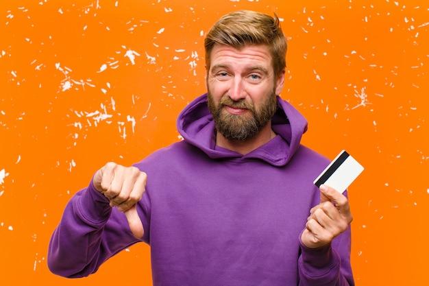 Jonge blondeman met een creditcard die een paarse hoodie draagt