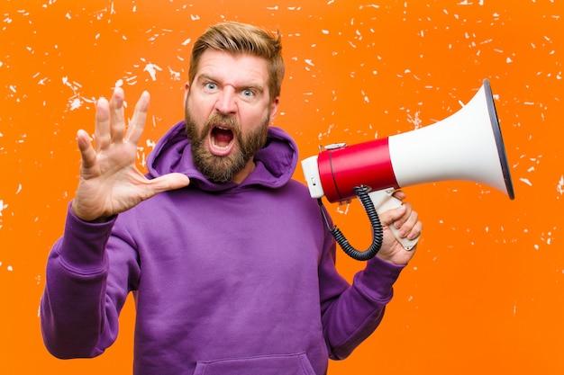Jonge blondeman met een megafoon die een paarse hoodie draagt tegen beschadigde oranje muur