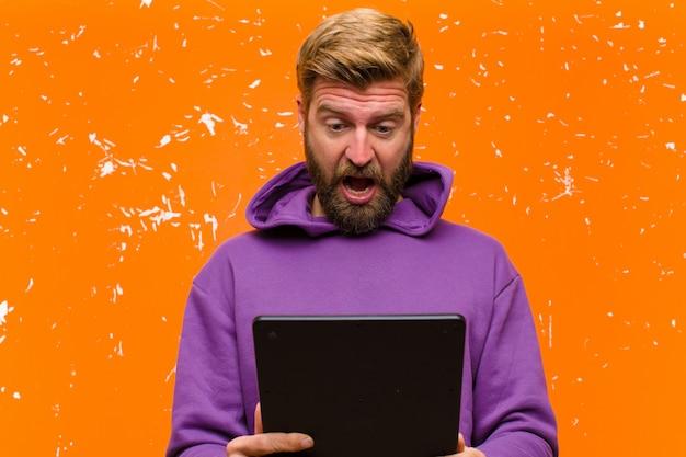 Jonge blondeman met een tablet die een paarse hoodie draagt tegen beschadigde oranje muur