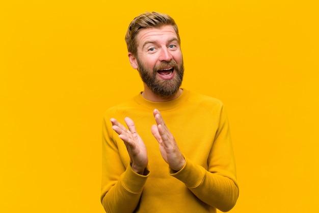 Jonge blondeman voelt zich gelukkig en succesvol, glimlachend en klappende handen, zeggen gefeliciteerd met een applaus tegen oranje muur
