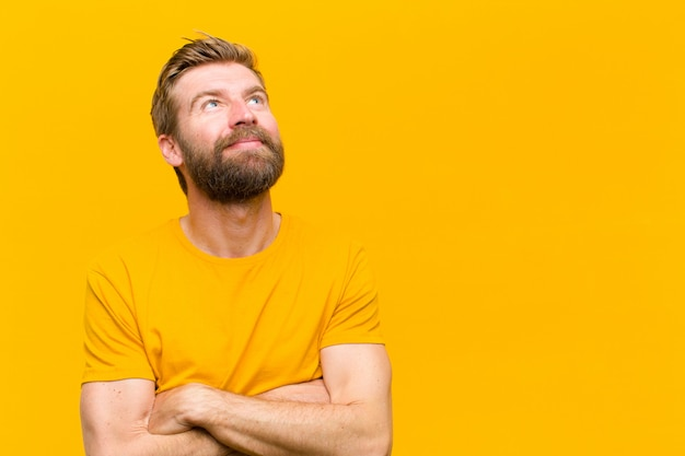 Jonge blondeman voelt zich gelukkig, trots en hoopvol, vraagt zich af of denkt, op zoek naar ruimte met gekruiste armen tegen oranje muur te kopiëren