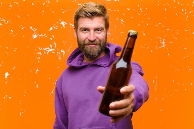 Jonge blondemens die een bier hebben die een purpere hoodie dragen tegen beschadigde oranje muur