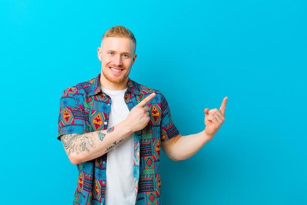 Jonge blondemens die een drukoverhemd dragen die gelukkig glimlachen en aan kant en naar omhoog met beide handen richten die voorwerp in exemplaarruimte tonen