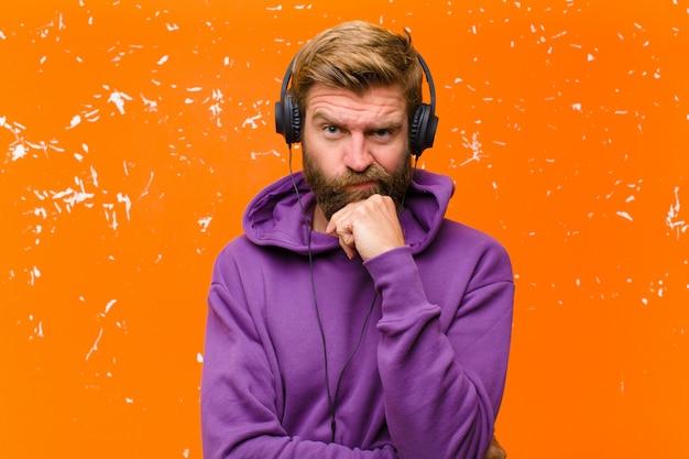 Jonge blondemens die en muziek met hoofdtelefoons dansen luisteren die een purpere hoodie dragen tegen beschadigde oranje muur