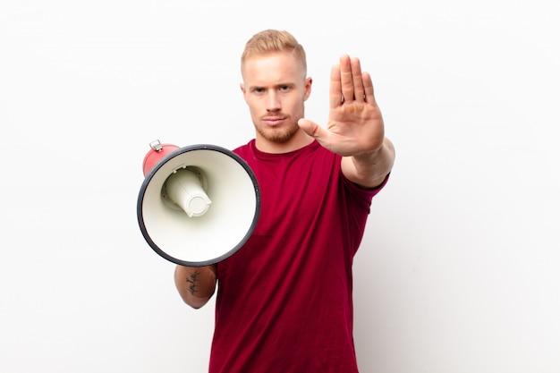Jonge blondemens die ernstig, streng, ontstemd en boos die open palm tonen die einde maken gebaar tegen witte muur met een megafoon