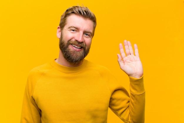 Jonge blondemens die gelukkig en vrolijk glimlachen, hand zwaaien, u welkom heten of begroeten, of vaarwel op oranje muur zeggen
