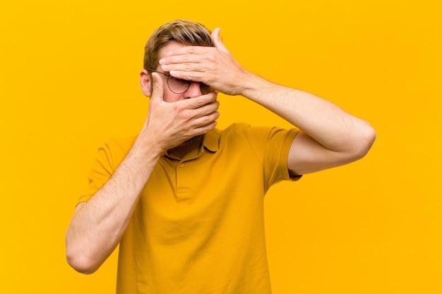 Jonge blondemens die gezicht behandelen met beide handen nr zeggen
