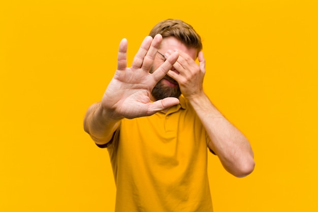 Jonge blondemens die gezicht behandelen met hand en andere hand vooraan zetten om camera tegen te houden, die foto's of beelden weigeren tegen oranje muur