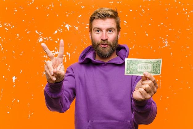 Jonge blondemens met dollarrekeningen of bankbiljetten die een purpere hoodie dragen tegen beschadigde sinaasappel