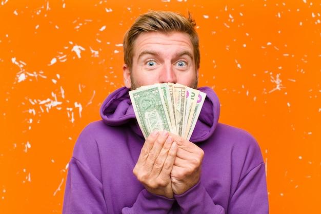 Jonge blondemens met dollarrekeningen of bankbiljetten die een purpere hoodie op beschadigde oranje muur dragen