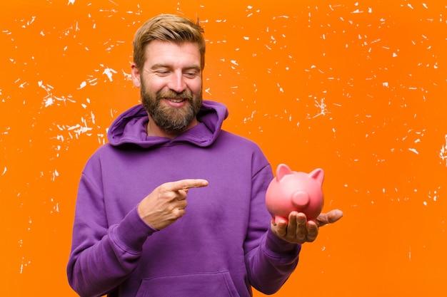 Jonge blondemens met een spaarvarken die een purpere hoodie dragen tegen beschadigde oranje muur