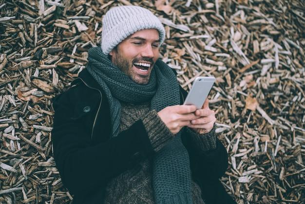 Jonge blondemens op de mobiele telefoon die op stukken van hout dichtbij het koninklijke paleis in madrid tijdens de winter liggen