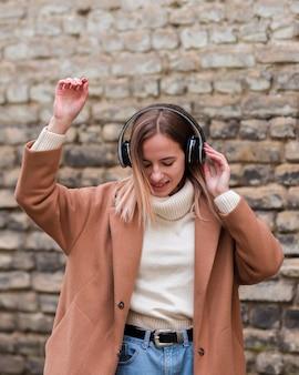 Jonge blondevrouw die aan muziek op hoofdtelefoons buiten luisteren