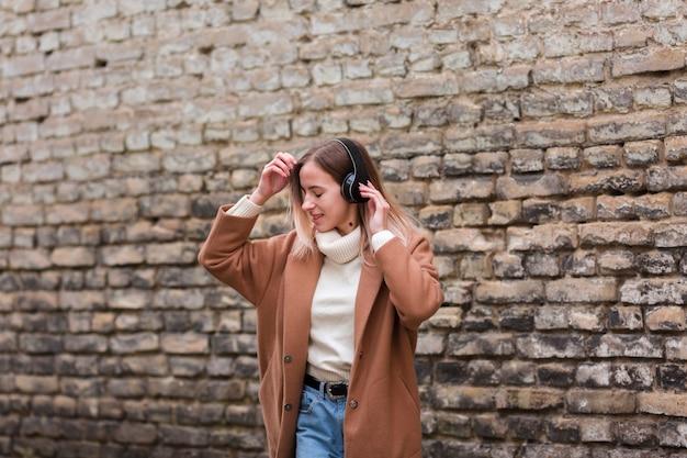 Jonge blondevrouw die aan muziek op hoofdtelefoons luisteren