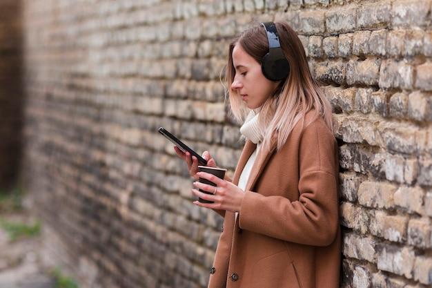 Jonge blondevrouw die aan muziek op hoofdtelefoons met exemplaarruimte luisteren