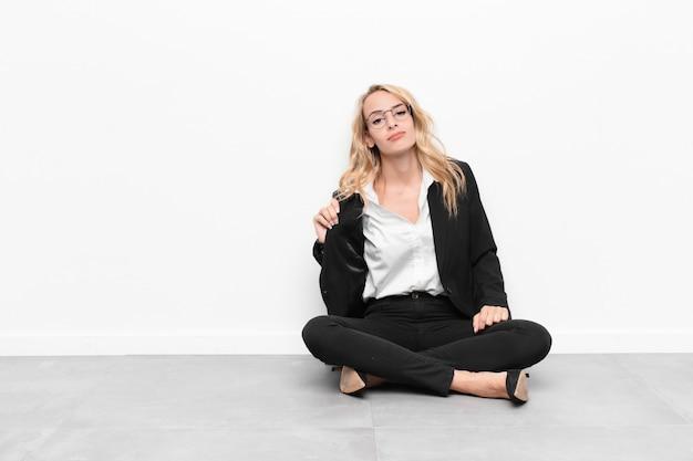 Jonge blondevrouw die arrogant, succesvol, positief en trots kijken, die aan zelfzitting op de vloer richten