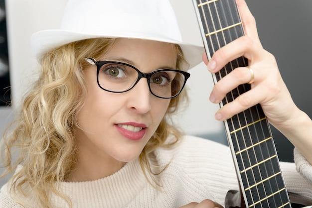 Jonge blondevrouw die de akoestische gitaar spelen