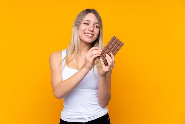 Jonge blondevrouw die een chocoladetablet nemen en gelukkig