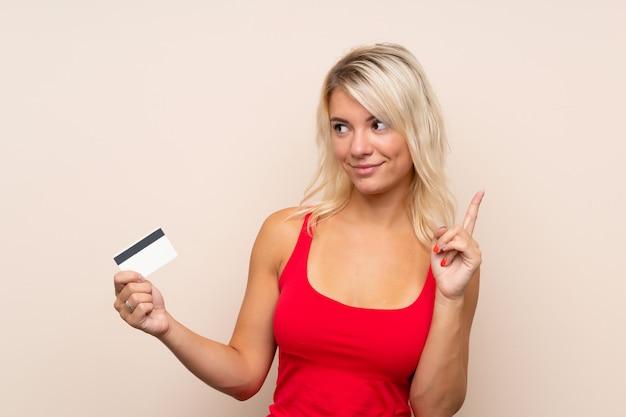 Jonge blondevrouw die een creditcard houden